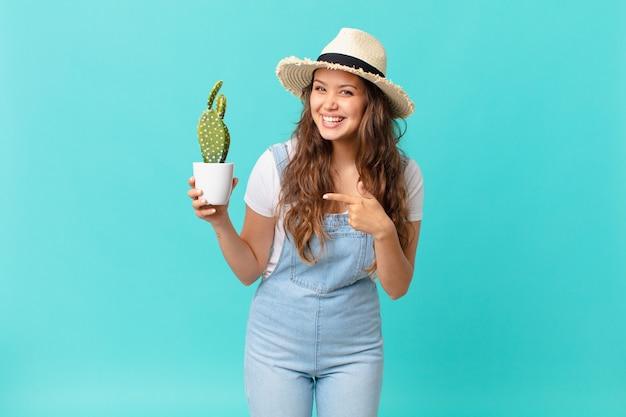 Młoda ładna kobieta wyglądająca na podekscytowaną i zaskoczoną, wskazując na bok i trzymająca kaktusa