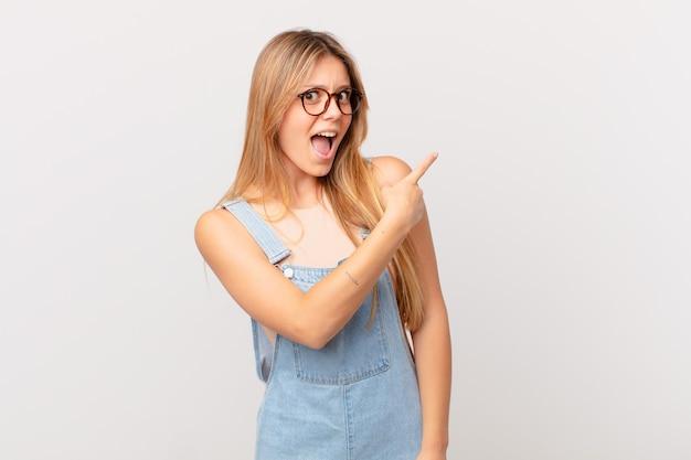 Młoda ładna kobieta wyglądająca na podekscytowaną i zaskoczoną, wskazując na bok