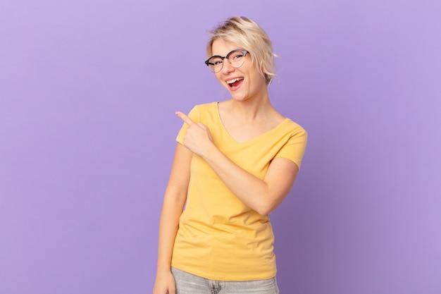 Młoda ładna kobieta wyglądająca na podekscytowaną i zdziwioną, wskazując na bok