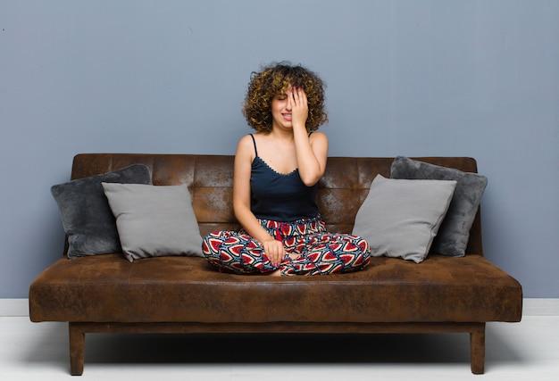 Młoda ładna kobieta wyglądająca na senną, znudzoną i ziewającą, z bólem głowy i dłonią zakrywającą połowę twarzy siedzącą na kanapie.