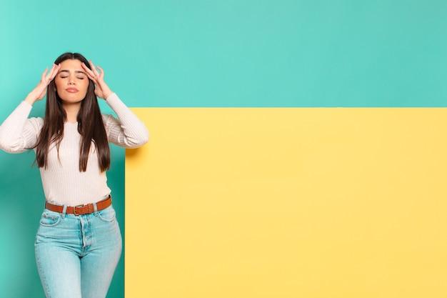 Młoda ładna kobieta wyglądająca na skoncentrowaną, zamyśloną i natchnioną, przeprowadzającą burzę mózgów i wyobrażającą sobie z rękami na czole. skopiuj miejsce, aby umieścić swoją koncepcję