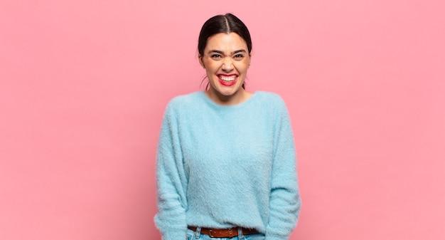 Młoda ładna kobieta wyglądająca na szczęśliwą i głupkowatą z szerokim, zabawnym, szalonym uśmiechem i szeroko otwartymi oczami