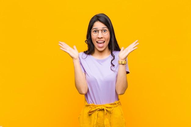Młoda ładna kobieta wyglądająca na szczęśliwą i podekscytowaną, zszokowaną niespodziewaną niespodzianką z otwartymi obiema rękami obok pomarańczowej ściany