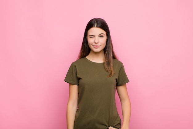 Młoda ładna kobieta wyglądająca na szczęśliwą i przyjazną, uśmiechającą się i mrugającą do ciebie okiem z pozytywnym nastawieniem do różowej ściany