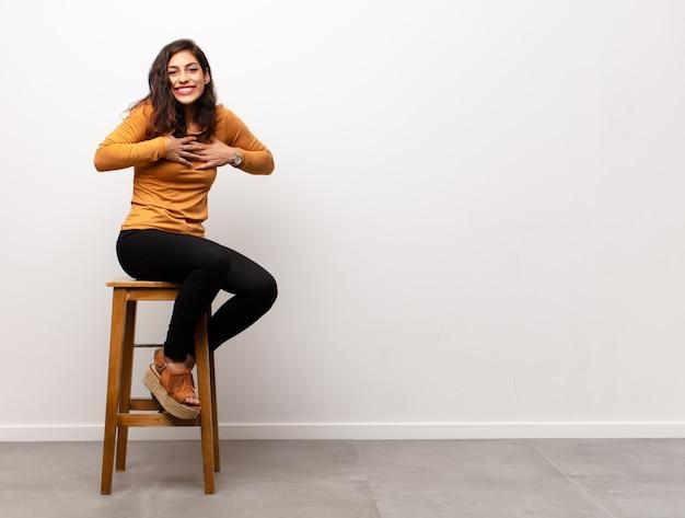 Młoda ładna kobieta wyglądająca na szczęśliwą i przyjazną, uśmiechającą się i mrugającą do ciebie okiem z pozytywnym nastawieniem, siedząc w pokoju