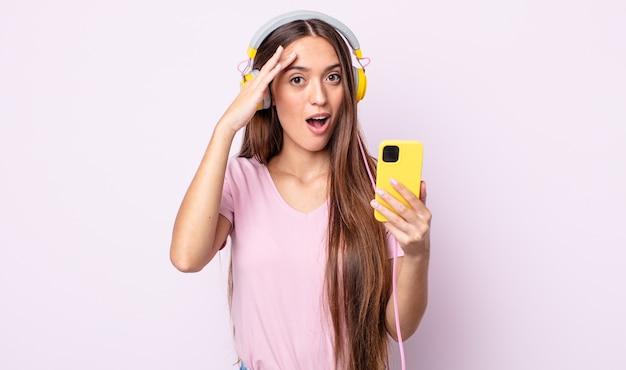 Młoda ładna kobieta wyglądająca na szczęśliwą, zdumioną i zdziwioną. słuchawki i smartfon