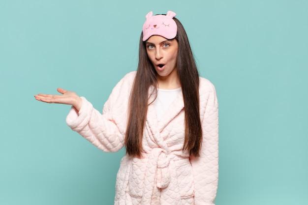 Młoda ładna kobieta wyglądająca na zaskoczoną i zszokowaną, z opuszczoną szczęką, trzymająca przedmiot z otwartą dłonią z boku. budząc się w koncepcji piżamy