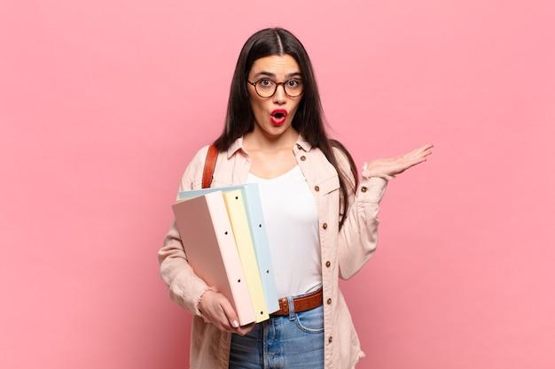 Młoda ładna kobieta wyglądająca na zaskoczoną i zszokowaną, z opuszczoną szczęką, trzymająca przedmiot z otwartą dłonią z boku. koncepcja studenta