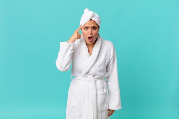 Młoda ładna kobieta wyglądająca na zaskoczoną, realizującą nową myśl, pomysł lub koncepcję i noszącą szlafrok po prysznicu