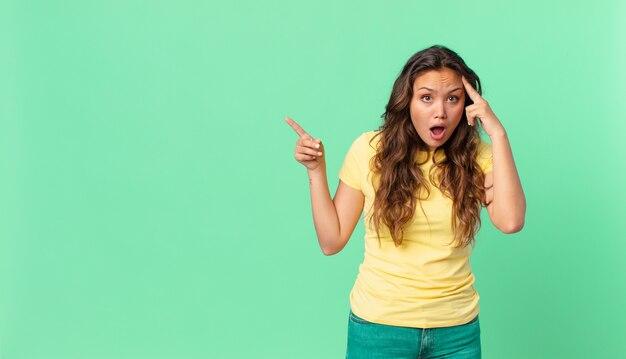 Młoda ładna kobieta wyglądająca na zaskoczoną, realizującą nową myśl, pomysł lub koncepcję i wskazującą na miejsce kopiowania