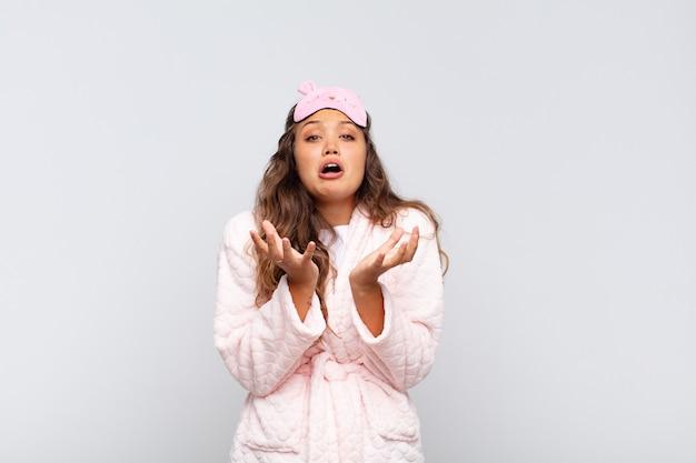 Młoda ładna kobieta wyglądająca na zdesperowaną i sfrustrowaną, zestresowaną, nieszczęśliwą i zirytowaną, krzyczącą i wrzeszczącą w piżamie