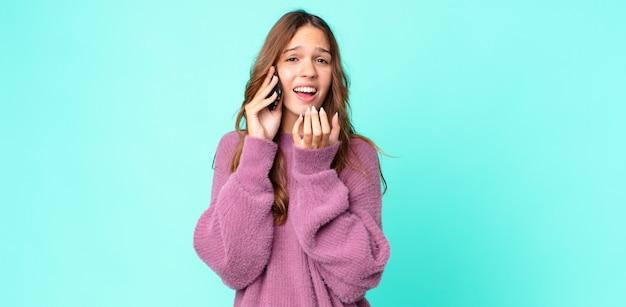 Młoda ładna kobieta wyglądająca na zdesperowaną, sfrustrowaną i zestresowaną, która korzysta ze smartfona