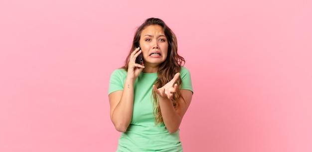 Młoda ładna kobieta wyglądająca na zdesperowaną, sfrustrowaną i zestresowaną, trzymająca smartfona