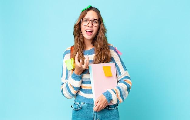 Młoda ładna kobieta wyglądająca na zdesperowaną, sfrustrowaną i zestresowaną z torbą i trzymającą książki