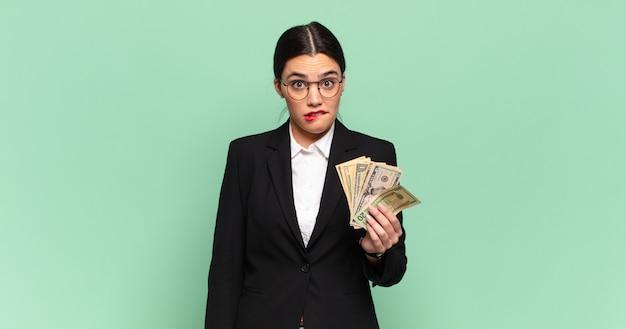 Młoda ładna kobieta wyglądająca na zdziwioną i zdezorientowaną, przygryza wargę nerwowym gestem, nie znając odpowiedzi na problem. koncepcja biznesu i banknotów