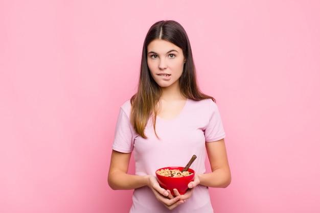 Młoda ładna kobieta wyglądająca na zdziwioną i zdezorientowaną, przygryzającą wargę nerwowym gestem, nie znającą odpowiedzi na problem z miską śniadaniową