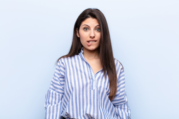 Młoda ładna kobieta wyglądająca na zdziwioną i zdezorientowaną, przygryzającą wargę nerwowym gestem, nie znającą odpowiedzi na problem