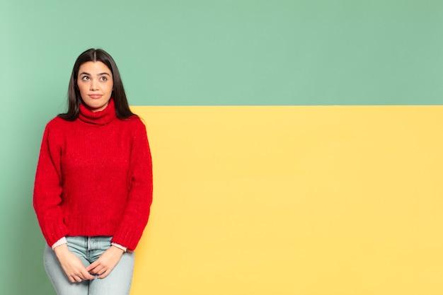 Młoda ładna kobieta wyglądająca na zdziwioną i zdezorientowaną, zastanawiającą się lub próbującą rozwiązać problem lub myśląc. skopiuj miejsce, aby umieścić swoją koncepcję