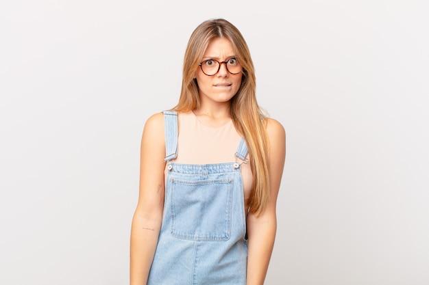 Młoda ładna Kobieta Wyglądająca Na Zdziwioną I Zdezorientowaną Premium Zdjęcia