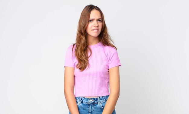 Młoda ładna kobieta wyglądająca na zdziwioną i zdezorientowaną
