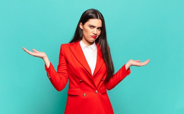 Młoda ładna kobieta wyglądająca na zdziwioną, zdezorientowaną i zestresowaną, zastanawiającą się między różnymi opcjami, niepewną. pomysł na biznes