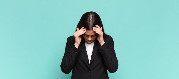 Młoda ładna kobieta wyglądająca na zestresowaną i sfrustrowaną, pracująca pod presją, z bólem głowy i z problemami. pomysł na biznes