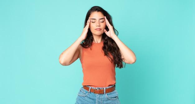 Młoda ładna kobieta wyglądająca na zestresowaną i sfrustrowaną, pracująca pod presją, z bólem głowy i z problemami