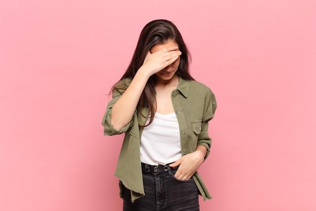 Młoda ładna kobieta wyglądająca na zestresowaną, zawstydzoną lub zdenerwowaną, z bólem głowy, zakrywająca twarz ręką