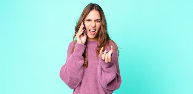 Młoda ładna kobieta wyglądająca na złą, zirytowaną i sfrustrowaną, używająca smartfona
