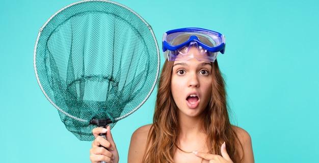 Młoda ładna kobieta wyglądająca na zszokowaną i zaskoczoną z szeroko otwartymi ustami, wskazującą na siebie goglami i siecią rybacką