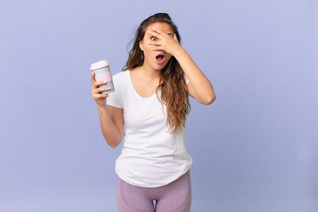 Młoda ładna kobieta wyglądająca na zszokowaną, przestraszoną lub przerażoną, zakrywająca twarz dłonią i trzymająca kawę