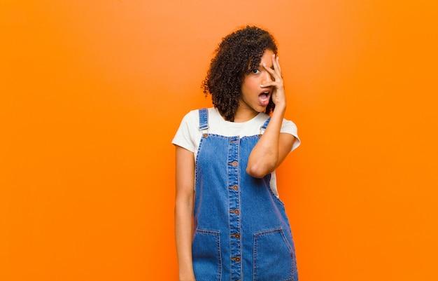 Młoda ładna kobieta wyglądająca na zszokowaną, przestraszoną lub przerażoną, zakrywającą twarz dłonią i zerkającą między palcami na pomarańczową ścianę