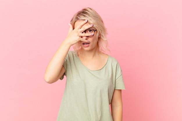 Młoda ładna kobieta wyglądająca na zszokowaną, przestraszoną lub przerażoną, zakrywająca twarz dłonią