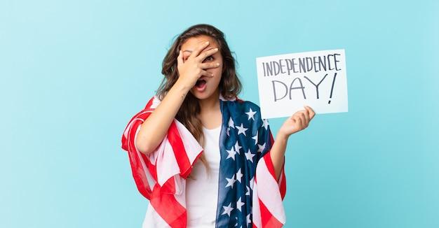 Młoda ładna kobieta wyglądająca na zszokowaną, przestraszoną lub przerażoną, zakrywającą twarz koncepcją dnia niepodległości dłoni