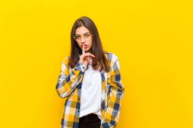 Młoda ładna kobieta wyglądająca poważnie i skrzyżowana palcem na ustach, domagająca się ciszy lub spokoju, trzymająca sekret nad pomarańczową ścianą