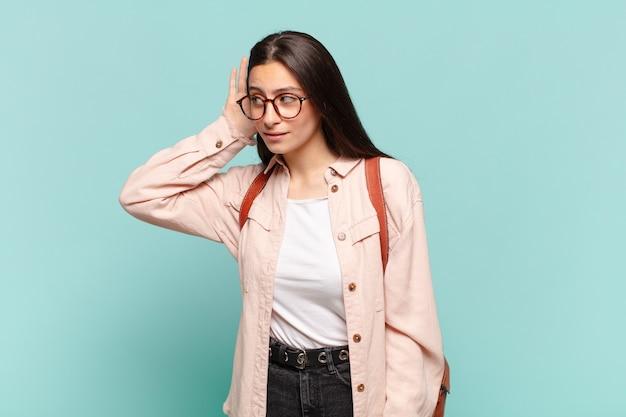 Młoda ładna kobieta wyglądająca poważnie i zaciekawiona, słuchająca, próbująca usłyszeć tajną rozmowę lub plotkę, podsłuchująca. koncepcja studenta