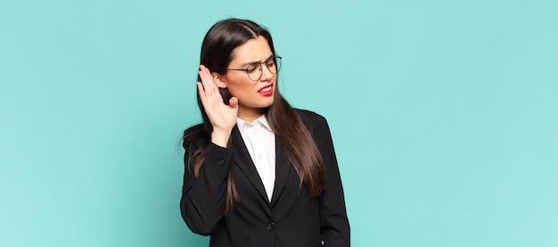 Młoda ładna kobieta wyglądająca poważnie i zaciekawiona, słuchająca, próbująca usłyszeć tajną rozmowę lub plotkę, podsłuchująca