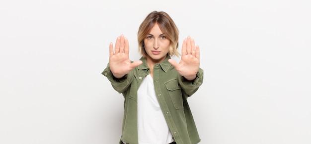 Młoda ładna kobieta wyglądająca poważnie, nieszczęśliwie, zła i niezadowolona, zakazująca wejścia lub mówiąca stop z otwartymi dłońmi