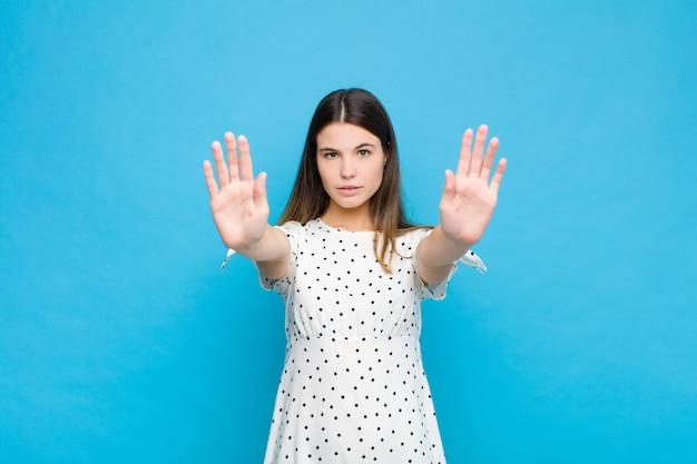 Młoda ładna kobieta, wyglądająca poważnie, niezadowolona, zła i niezadowolona, zabraniająca wejścia obiema otwartymi dłońmi o niebieską ścianę