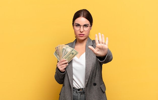 Młoda ładna kobieta wyglądająca poważnie, surowo, niezadowolona i zła, pokazując otwartą dłoń, robiąc gest zatrzymania