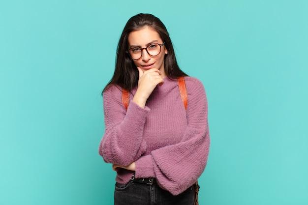 Młoda ładna kobieta wyglądająca poważnie, zdezorientowana, niepewna i zamyślona, wątpiąca w opcje lub wybory. koncepcja studenta
