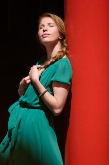 Młoda ładna kobieta wygrzewa się w słońcu z zamkniętymi oczami w zieleni sukni, kopii przestrzeń