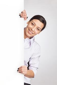 Młoda ładna kobieta wyłania się z boku billboardu.