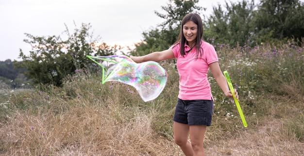 Młoda ładna kobieta wypuszcza duże kolorowe bańki mydlane wśród trawy na łonie natury.