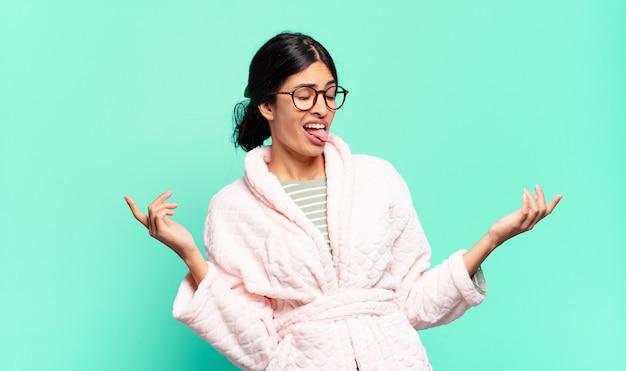 Młoda ładna kobieta wzrusza ramionami z głupim, szalonym, zdezorientowanym, zdziwionym wyrazem twarzy, zirytowana i nieświadoma. koncepcja piżamy
