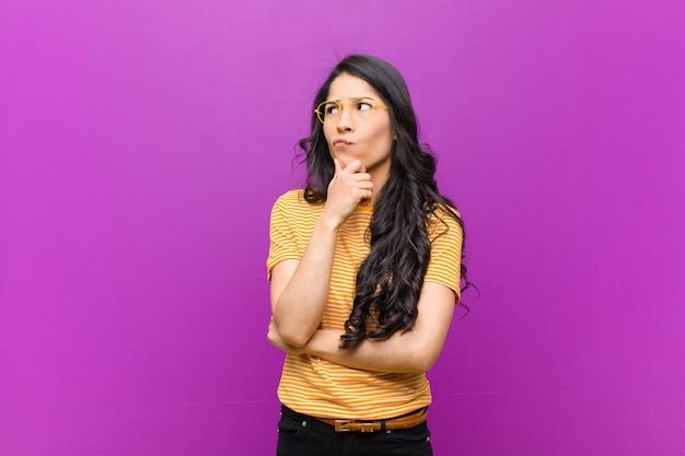 Młoda ładna kobieta z ameryki łacińskiej, czująca się niepewnie i zdezorientowana, z różnymi opcjami, zastanawiająca się, jaką decyzję podjąć przeciwko fioletowej ścianie