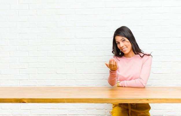 Młoda ładna kobieta z ameryki łacińskiej, czująca się szczęśliwa, odnosząca sukcesy i pewna siebie, stojąca przed wyzwaniem i mówiąca: przynieś to! witaj, siedząc przed stołem