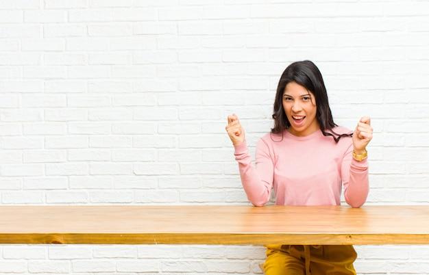 Młoda ładna kobieta z ameryki łacińskiej czująca się szczęśliwa, pozytywna i odnosząca sukcesy, świętująca zwycięstwo, osiągnięcia lub powodzenia siedząca przed stołem