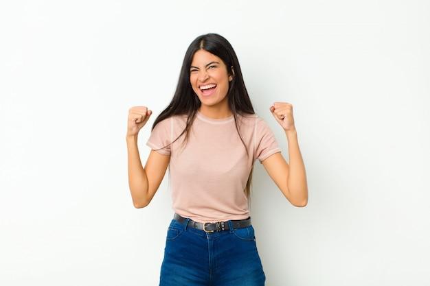 Młoda ładna kobieta z ameryki łacińskiej czuje się szczęśliwa, pozytywna i udana, świętuje zwycięstwo, osiągnięcia lub powodzenia przeciwko płaskiej ścianie