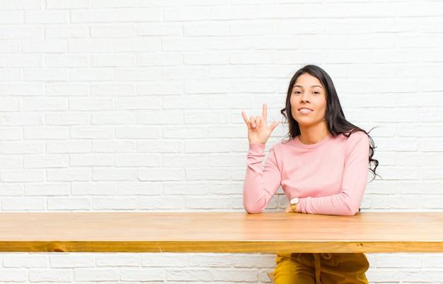 Młoda, ładna kobieta z ameryki łacińskiej czuje się szczęśliwa, zabawna, pewna siebie, pozytywna i zbuntowana, robiąc znak rocka lub heavy metalu ręką siedzącą przed stołem